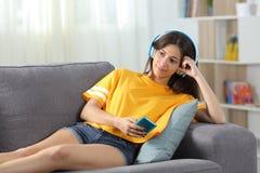 Avkopplat tonårigt lyssna till musik på en soffa arkivfoto