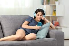 Avkopplat tonårigt lyssna till musik som ligger på en soffa royaltyfri foto