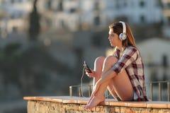 Avkopplat tonårigt lyssna till musik som sitter på en avsats arkivbild