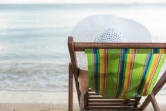 Avkoppling för lopp för kvinnaflicka lyxig på den tropiska stranden för stol Arkivfoto