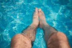 Avkoppling för ung man på simbassängen med hans ben i wen royaltyfri bild