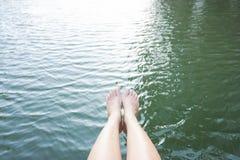 Avkoppling, genom att sätta, lägger benen på ryggen in i vatten Royaltyfri Foto