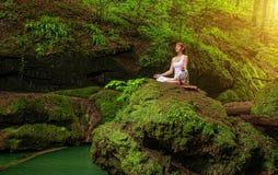 Avkoppling i skog på vattenfallet Ardha Padmasana poserar royaltyfria bilder