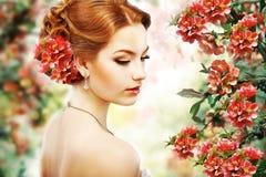 Avkoppling. Profil av röd hårskönhet över naturlig blom- bakgrund. Natur. Blomning arkivbilder