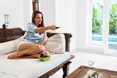 avkoppling rekreation Kvinna som kopplar av, hållande ögonen på TV television arkivbild
