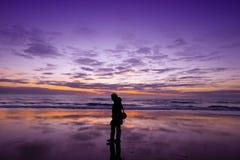 Avkoppling som går på stranden på solnedgången Royaltyfri Bild
