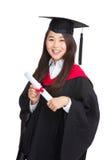 Avlägga examen studentflickan med den akademiska kappan Arkivbild