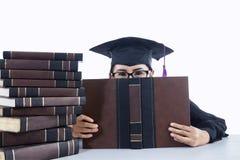 Avlägga examen studentflickan som täcker hennes framsida på vit bakgrund Fotografering för Bildbyråer