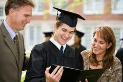 Avläggande av examen: Den stolta familjen beundrar diplomet royaltyfri fotografi