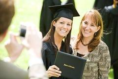 Avläggande av examen: Flickan poserar med mamman för bild royaltyfri fotografi