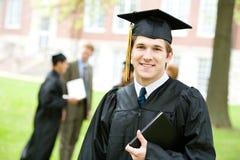 Avläggande av examen: Smart kandidat med andra bakom Royaltyfria Foton