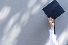 Avläggande av examenbegrepp Hon rymmer avläggande av examenlocket att att fira arkivfoton