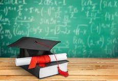 Avläggande av examenhatt med tofsen, diplom med rött royaltyfria foton