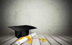 Avläggande av examenhatt och diplom på träbakgrund arkivfoton