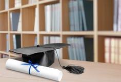 Avläggande av examenhatt och diplom på träbakgrund royaltyfri foto