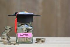 Avläggande av examenhatt på glasflaskan med bunten av myntpengar på trä royaltyfri fotografi
