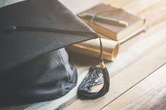 avläggande av examenlock, hatt med gradpapper på wood tabellavläggande av examen c royaltyfri bild