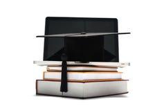 Avläggande av examenlock och bok med bärbara datorn royaltyfri foto
