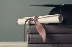Avläggande av examenlock, snirkel och böcker - urblekta signaler arkivfoto