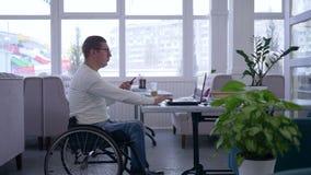 Avlägsen affärsledning, den handikappade mannen i rullstol använder en mobiltelefon som sitter på tabellen med bärbara datorn i k arkivfilmer