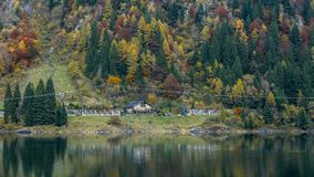 Avlägsen byggnad och färgrika träd reflekterade i den alpina sjön Aut royaltyfri foto