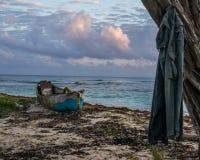 Avlägsen jamaikansk strand med den övergav fiskebåten och skjortan på träd arkivfoto