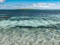 Avlägsen sikt av holmen av Papay som ses från kusten av Papa Westray, Orkney Royaltyfri Foto