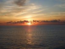 Avlägsen solnedgång reflekterad på vattnet royaltyfri foto