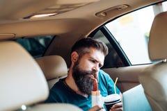 Avlägset arbete kaffe mer tid snabbmat - varmkorv skäggig man Mogen hipster med skägget Manlig barberareomsorg Brutal hipster fotografering för bildbyråer