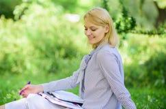 Avlägset jobbbegrepp Klara av avlägsen det fria för affär Kvinnan med bärbara datorn sitter gräsängen Bästa jobb att arbeta avläg royaltyfri bild
