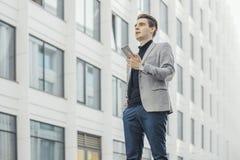 Avlägset plan av den unga affärsmannen som talar vid mobiltelefonen bredvid skyskrapa royaltyfria bilder