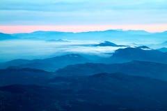 Avlägsna berg med blå ogenomskinlighet och moln arkivfoto