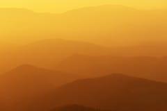 Avlägsna berg på solnedgången Arkivfoto