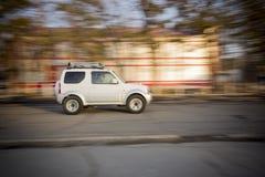Avlägsna Spassk, Primorsky Krai, Ryssland - April 1, 2013: Vita SUV på snabb körning på vägen i staden Rörelseeffektfoto Royaltyfri Bild