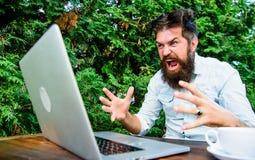 Avl?gset jobb i Hipster som ?r upptagen med frilans- Wifi och b?rbar dator L?ngsamt irritera f?r internet arkivfoto