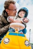 Avla att krama hans son som sitter i bilen Royaltyfria Foton