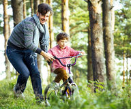Avla att lära hans son för att rida på cykeln utanför, den verkliga lyckliga familjen, livsstilfolkbegrepp Royaltyfri Fotografi