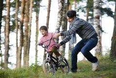 Avla att lära hans son för att rida på cykeln utanför Arkivfoton