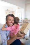 Avla att omfamna sonen, medan motta gåvan i vardagsrum Arkivbilder