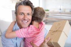 Avla att omfamna sonen, medan motta gåvan i vardagsrum Royaltyfria Bilder
