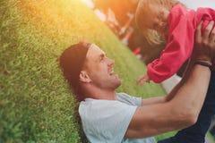 Avla att rymma hans dotter i armar i parkera lycklig tid för familj Arkivbilder