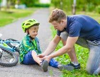 Avla att sätta musikband-hjälpmedlet på unga pojkens skada som avverkar av hans b arkivbild