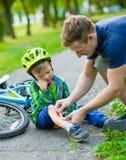 Avla att sätta musikband-hjälpmedlet på unga pojkens skada som avverkar av hans cykel arkivfoton