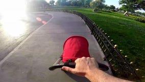 Avla att skjuta en behandla som ett barnsittvagn från handtagstång i stads- trottoar stock video