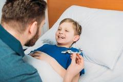 Avla att spela med den sjuka pysen som ligger i sjukhussäng, farsa och son i sjukhus royaltyfri bild