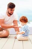Avla att spela med hans lilla son på golvet fotografering för bildbyråer
