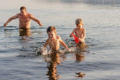 Avla att spela med två barn i sjön i sommar, lycklig familj på sommarsemester royaltyfria foton