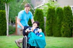 Avla att springa omkring parkerar med den rörelsehindrade sonen i rullstol Fotografering för Bildbyråer