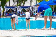 Avla att undervisa hans döttrar att dyka i pöl på arkivfoto