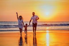 Avla, fostra, behandla som ett barn har en gyckel på solnedgångstranden Arkivfoto